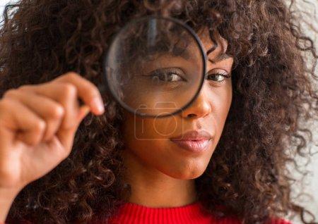 Photo pour Curieuse femme afro-américaine regardant à travers la loupe avec une expression confiante sur la pensée intelligente visage grave - image libre de droit