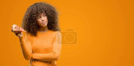 Photo pour Femme afro-américaine avec une tranche de pizza visage sérieux en pensant à la question, idée très confuse - image libre de droit