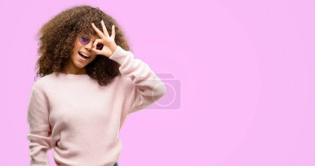African american woman wearing a pink sweater with happy face smiling doing ok sign with hand on eye looking through fingers
