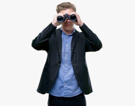 Photo pour Jeune homme blond beau regardant à travers des jumelles avec une expression confiante sur la pensée intelligente du visage sérieux - image libre de droit