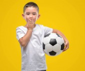 Dark haired little child playing with soccer ball cover mouth with hand shocked with shame for mistake, expression of fear, scared in silence, secret concept