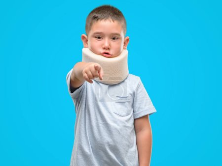 Dark haired little child injured wearing neck collar pointing with finger to the camera and to you, hand sign, positive and confident gesture from the front