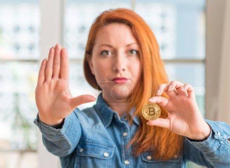 Photo pour Femme rousse tenant bitcoin cryptocurrency à la maison avec la main ouverte, faisant signe d'arrêt avec l'expression grave et confiante, geste de défense - image libre de droit