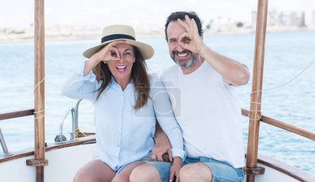 Middle age couple traveling on sailboat with happy face smiling doing ok sign with hand on eye looking through fingers