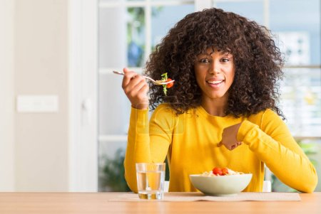Photo for African american woman eating pasta salad at home with surprise face pointing finger to himself - Royalty Free Image