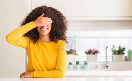African american woman wearing yellow sweater at kitchen smiling and laughing with hand on face covering eyes for surprise. Blind concept.