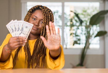 Photo for African american woman holding dollars with open hand doing stop sign with serious and confident expression, defense gesture - Royalty Free Image