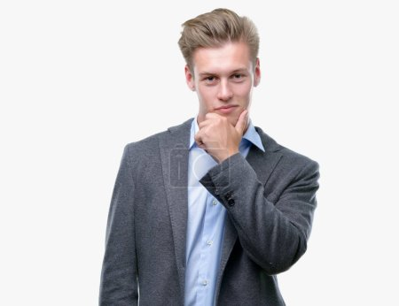 Young handsome blond business man looking confident at the camera with smile with crossed arms and hand raised on chin. Thinking positive.