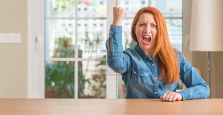 Redhead woman at home angry and mad raising fist frustrated and furious while shouting with anger. Rage and aggressive concept.
