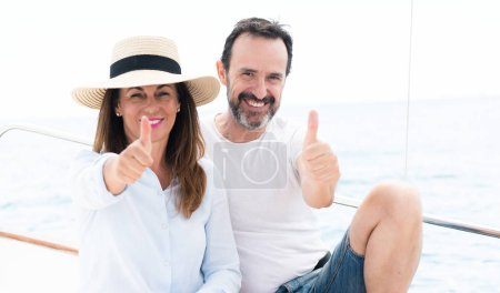 Middle age couple traveling on sailboat happy with big smile doing ok sign, thumb up with fingers, excellent sign