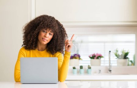 African american woman using computer laptop at kitchen very happy pointing with hand and finger to the side