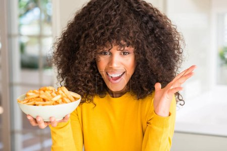 African american woman holding a plate with potato chips at home very happy and excited, winner expression celebrating victory screaming with big smile and raised hands