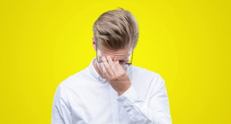 Young handsome blond man tired rubbing nose and eyes feeling fatigue and headache. Stress and frustration concept.
