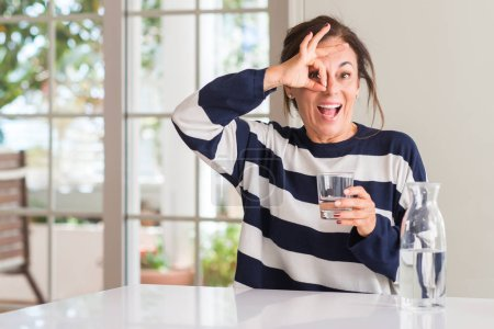 Middle aged woman drinking a glass of water with happy face smiling doing ok sign with hand on eye looking through fingers