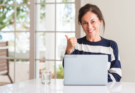 Photo for Middle aged woman using laptop at home pointing with hand and finger up with happy face smiling - Royalty Free Image
