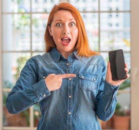 Photo pour Femme rousse à l'aide de smartphone à domicile pointant très heureux avec la main et des doigts - image libre de droit