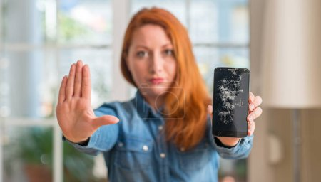 Redhead woman holding broken smartphone with open hand doing stop sign with serious and confident expression, defense gesture