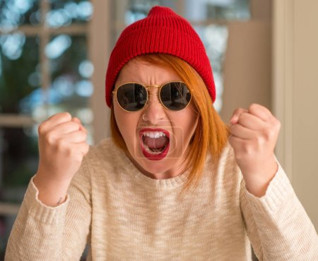 Stylish redhead woman wearing wool cap and sunglasses annoyed and frustrated shouting with anger, crazy and yelling with raised hand, anger concept