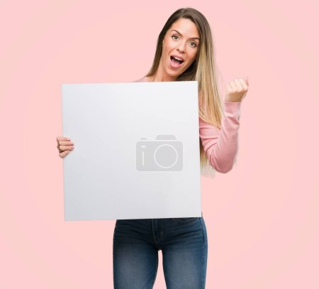Photo for Beautiful young woman holding advertising banner screaming proud and celebrating victory and success very excited, cheering emotion - Royalty Free Image