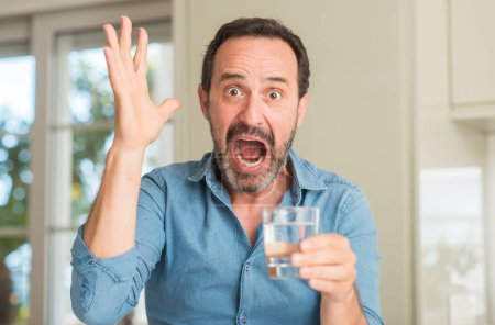 Middle age man drinking a glass of water very happy and excited, winner expression celebrating victory screaming with big smile and raised hands