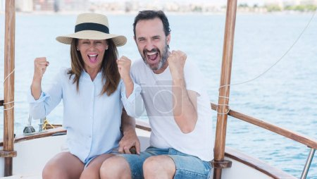 Middle age couple traveling on sailboat screaming proud and celebrating victory and success very excited, cheering emotion
