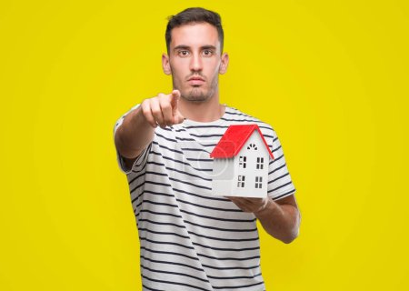 Handsome real estate agent holding a house pointing with finger to the camera and to you, hand sign, positive and confident gesture from the front