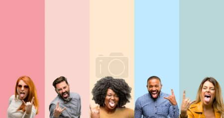 Photo for Cool group of people, woman and man making rock symbol with hands, shouting and celebrating with tongue out - Royalty Free Image