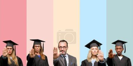 Photo pour Professeur principal avec ses étudiants diplômés ennuyé avec mauvaise attitude faisant arrêt signe avec la main, dire non, exprimer la sécurité, de défense ou de restriction, poussant peut-être - image libre de droit