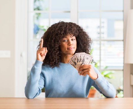 African american woman holding dollar bank notes surprised with an idea or question pointing finger with happy face, number one