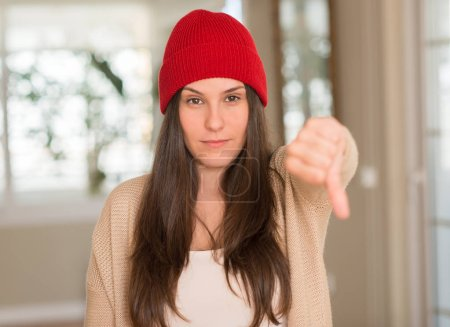 Young beautiful woman wearing red cap at home with angry face, negative sign showing dislike with thumbs down, rejection concept