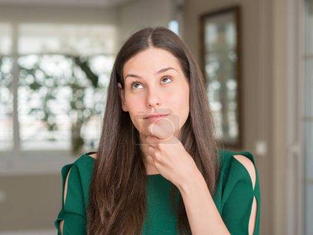 Photo pour Jeune belle femme à la maison visage sérieux penser à la question, idée très confuse - image libre de droit