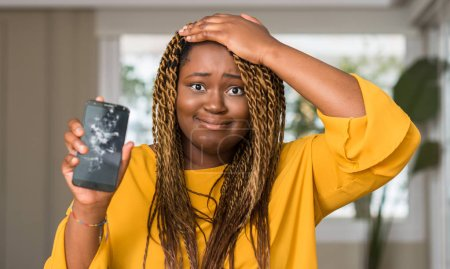 African american woman showing broken smartphone stressed with hand on head, shocked with shame and surprise face, angry and frustrated. Fear and upset for mistake.