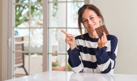 Photo for Middle aged woman eating chocolate bar very happy pointing with hand and finger to the side - Royalty Free Image