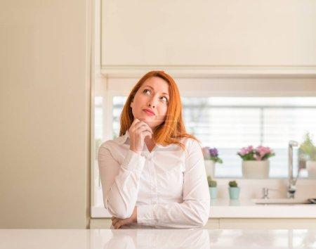 Photo pour Femme rousse à la cuisine avec la main sur le menton réflexion sur la question, expression pensive. Sourire avec le visage pensif. Notion de doute. - image libre de droit
