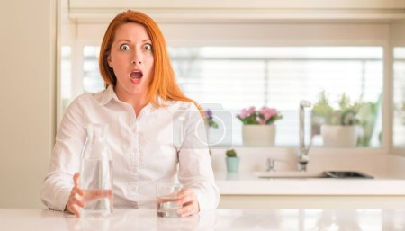 Thirsty redhead woman and glass of water scared in shock with a surprise face, afraid and excited with fear expression