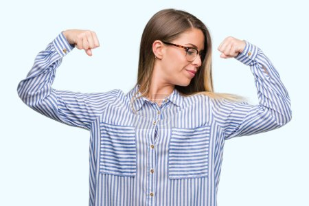 Beautiful young woman wearing elegant shirt and glasses showing arms muscles smiling proud. Fitness concept.