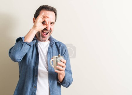 Senior man drinking coffee in a mug with happy face smiling doing ok sign with hand on eye looking through fingers