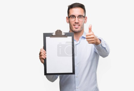 Handsome young business man showing a clipboard happy with big smile doing ok sign, thumb up with fingers, excellent sign