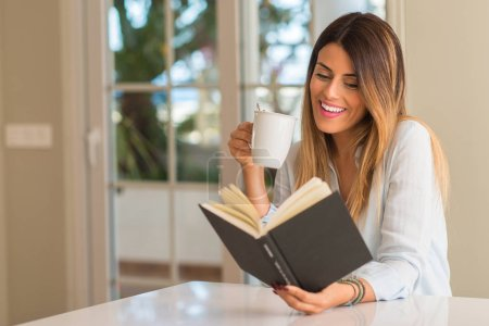 Beautiful young woman reading a book smiling and relaxing drinking a cup of coffee at home.