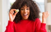 African american woman holding macaron screaming proud and celebrating victory and success very excited, cheering emotion