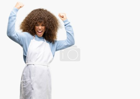 African american shop owner woman wearing an apron happy and excited celebrating victory expressing big success, power, energy and positive emotions. Celebrates new job joyful