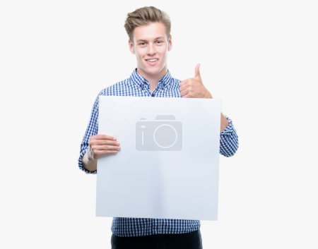 Young handsome blond man holding a banner happy with big smile doing ok sign, thumb up with fingers, excellent sign