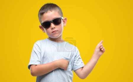 Dark haired little child wearing sunglasses very happy pointing with hand and finger to the side