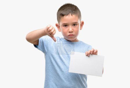 Dark haired little child holding a blank card with angry face, negative sign showing dislike with thumbs down, rejection concept