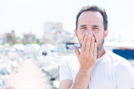 Handsome middle age man in marina cover mouth with hand shocked with shame for mistake, expression of fear, scared in silence, secret concept