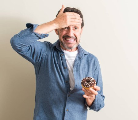 Photo for Senior man eating chocolate donut stressed with hand on head, shocked with shame and surprise face, angry and frustrated. Fear and upset for mistake. - Royalty Free Image