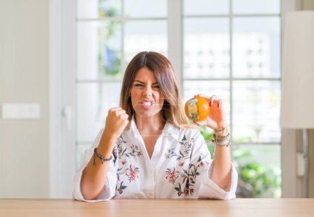 Young woman at home holding rotten orange annoyed and frustrated shouting with anger, crazy and yelling with raised hand, anger concept