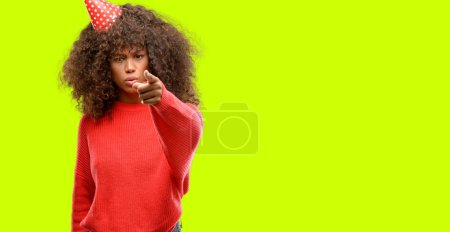 African american woman celebrates birthday pointing with finger to the camera and to you, hand sign, positive and confident gesture from the front