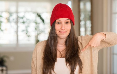 Photo pour Jeune belle femme portant une casquette rouge à la maison avec un visage surprise pointant du doigt vers lui-même - image libre de droit