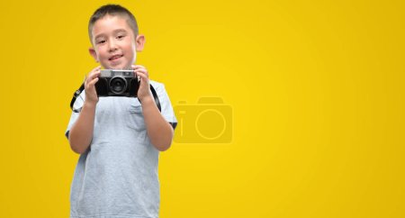 Dark haired little child holding vintage camera with a happy face standing and smiling with a confident smile showing teeth